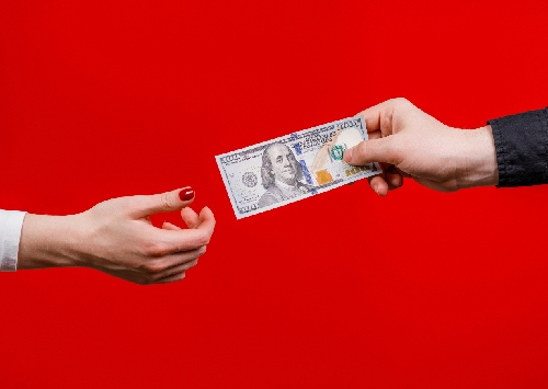 image of two hands passing money symbolizing how to transfer money from one bank to another
